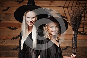 Halloween Concept - Closeup beautiful caucasian mother and her daughter in witch costumes celebrating Halloween posing with curved