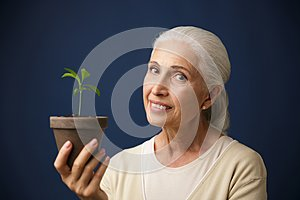 Photo of cheerful aged woman holding young plant in the spot, lo