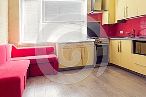 Yellow kitchen with cupboards, window, laminate and red soft cou