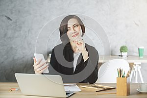 Beautiful smiling businesswoman using smartphone at workplace