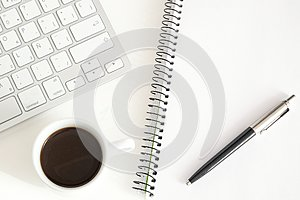 Notebook and keyboard next to a cup of coffee on a white desktop. Home working concept