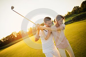 Couple playing golf together at sunset, swinging together to hit the ball with a golf club