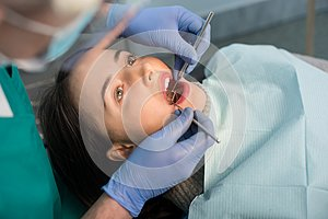Close up of woman having dental check up in dental clinic. Dentist examining a patient`s teeth with dental tools