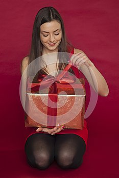 Woman in a red dress opens a gift