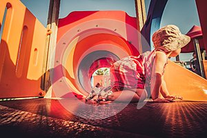 Vintage shot of baby profile crawling inside orange playground structure children point of view