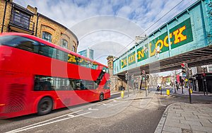 London, England - Iconic red double decker bus on the move at the world famous stables market of Camden Town