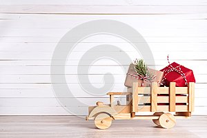 Christmas gift boxes in wooden toy truck on white wooden background.