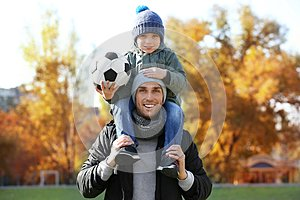 Father and son with ball on  pitch