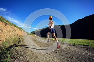 Fitness woman runner running on mountain trail
