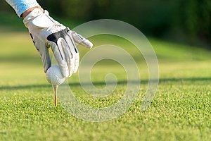 Hand asian woman putting golf ball on tee with club in golf course on sunny day for healthy sport.