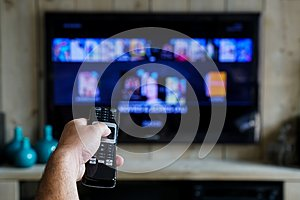 Hand with a remote control. Whats on tv, sliding through apps en movies on your television