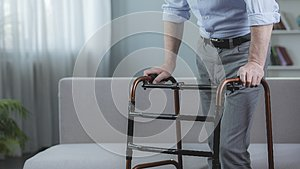 Handicapped person trying to move with walking frame at hospital, rehabilitation