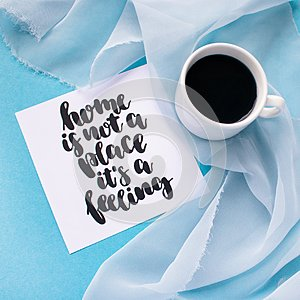 Mug of coffee on pale blue pastel chiffon cloth on a blue background. Card with handwritten inspirational quote Home is not a plac