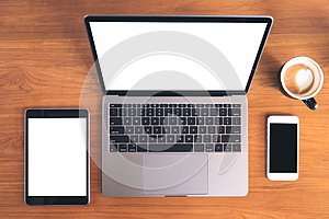 Top view mockup image of laptop with blank white screen , tablet pc , mobile phone and coffee cup