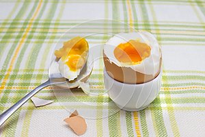 Boiled fresh smash broken egg for the breakfast on the porcelain stand for eggs. Broken beige hen egg and pieces of shells, bright