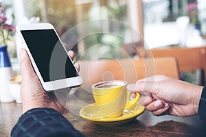 Mockup image of a hand holding white mobile phone with blank black desktop screen and yellow coffee cup on wooden table