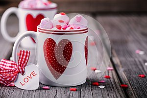 Hot cocoa with pink marshmallow in mugs with hearts for Valentine day