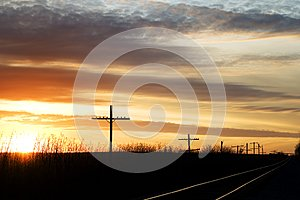 Railway next to the old telephone poles at sunset
