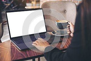 Mockup image of a businesswoman using laptop with blank white desktop screen while drinking hot coffee on wooden table