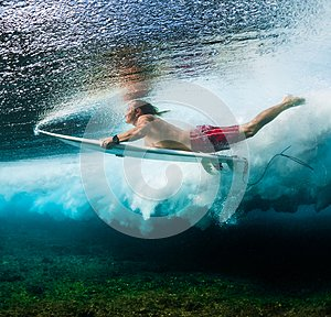 Young surfer dives under the ocean wave