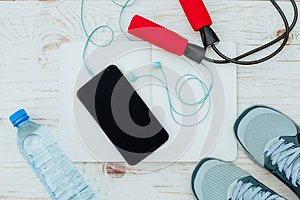 Fitness, healthy and active lifestyles Concept, Jump rope, dumbbells, sport shoes, bottle of water, smartphone with headphone