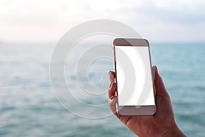 Mockup image of a hand holding and showing white mobile phone with blank black desktop screen in front of the sea and blue sky