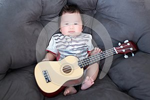Lovely baby sitting on the soft sofa with mini guitar. babies musician. Practice music skills for children. music and kids.