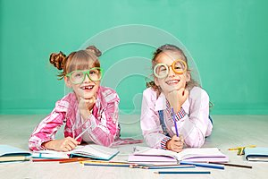 Two children laugh and read in glasses. The concept of childhood