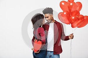 Young attactive African American couple holding heart balloon and paper.