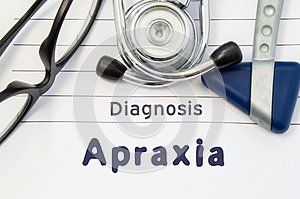 Neurological diagnosis of Apraxia. Neurological hammer, stethoscope and doctor`s glasses lie on doctor workplace on sheet of noteb