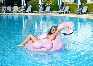 Woman in a swimming pool leisure on a giant inflatable giant pink flamingo float mattress in red bikini