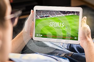 Man watching sports on tablet. Football and soccer game.
