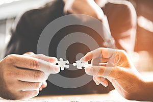 Businessman team work holding two jigsaw connecting couple puzzle piece for matching to goals target, success and start up new pro