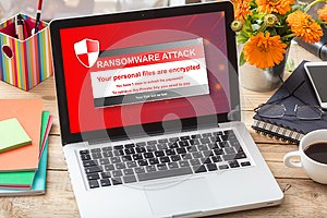 Ransomware attack message on a laptop screen on an office desk