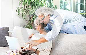 Senior retired couple using laptop computer at home on sofa - Elderly and technology concept with mature people watching shop