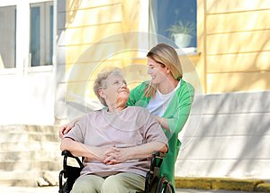 Disabled elderly woman and young caregiver outdoors
