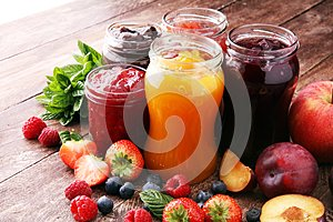 Assortment of jams, seasonal berries, plums, mint and fruits.