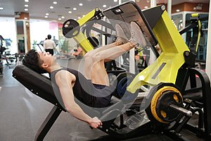 Asian chinese man in gym ,Fitness sport man Training of leg strength in the gym