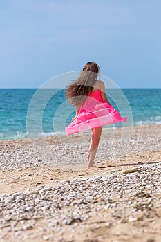 Girl in pink dress running along pebble beach