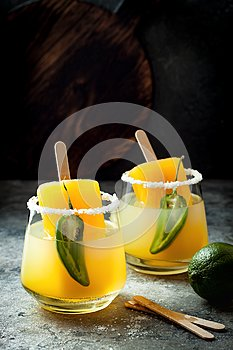 Spicy mango popsicle margarita cocktail with jalapeno and lime. Mexican alcoholic drink for Cinco de mayo party.