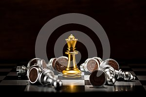 Gold queen chess surrounded by a number of fallen silver chess p