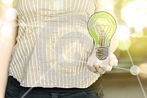 Woman holding a green light bulb with as `green thinking` concept on a sunny day