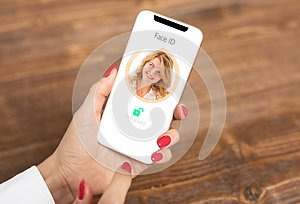 Woman using mobile phone`s facial recognition technology