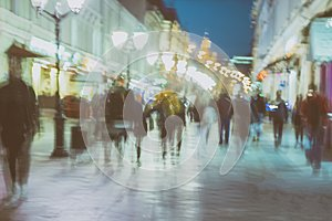 Abstract image of unrecognizable silhouettes of people walking in city street in evening, nightlife. Urban modern