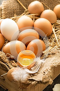 Bunch of fresh brown eggs in a wooden crate.