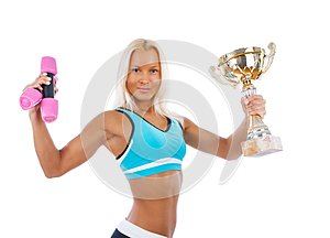 A woman holds a pair of dumbbells and a champion cup.
