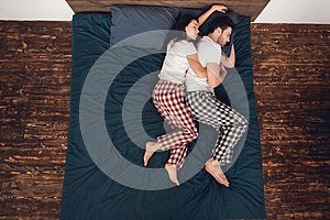 Top view. Young couple in pajamas sleeps close together on bed at home.