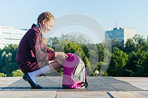 Girl in a school uniform opens a pink backpack for textbooks