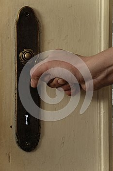 Close up of woman hand opens the old door