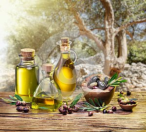 Olive berries in the wooden bowl and bottles of olive oil on the
